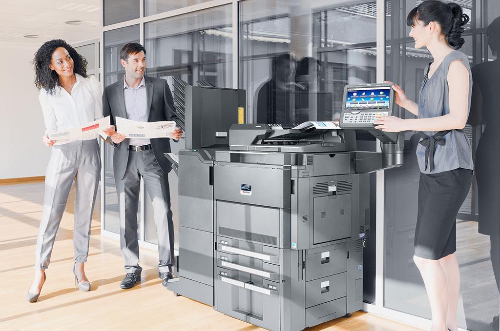 persone in un ufficio accanto ad una macchina fotocopiatrice
