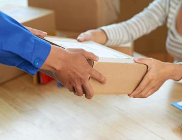 fattorino consegna un pacco a una donna