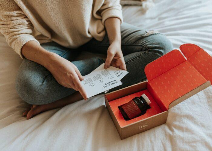donna seduta a gambe incrociate con un pacco aperto contenente un barattolo
